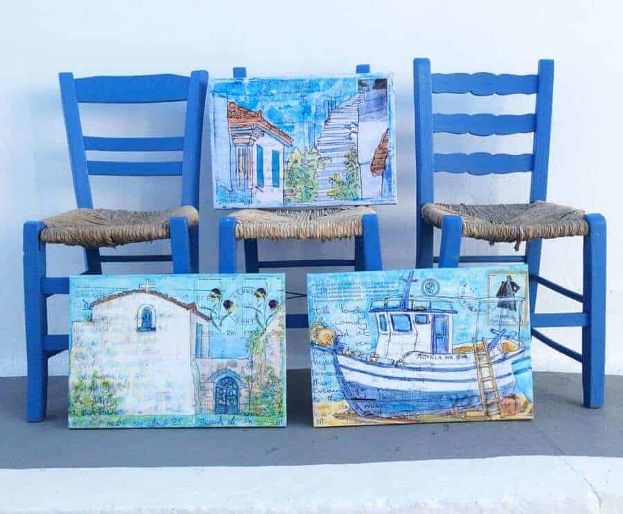 three blue greek taverna chairs with three canvases of greek art